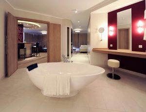 Blick aus dem Bad eines Hotelzimmers mit freistehender Wanne Richtung Bett