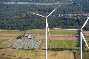 Windräder aus der Höhe gesehen mit Aussicht auf Wald und Ortschaft