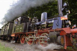 Fahrende Dampflokomotive mit aus dem Führerhaus schauenden Lokführer