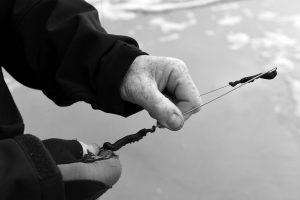 Hände eines alten Anglers beim Vorbereiten des Angelhakens
