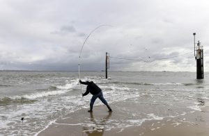 Angler am Strand wirft Angel ins Meer