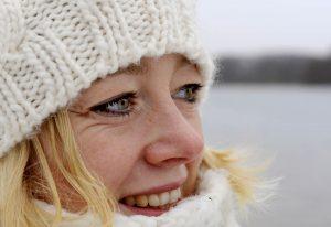 Nahprotrait blone Frau im Halbprofil mit weiße Mütze vor Schneelandschaft