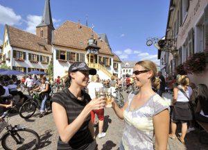 Zwei Frauen prosten sich inmitten von Radfahrernvor dem Deidesheimer Rathaus mit Weinschorle zu