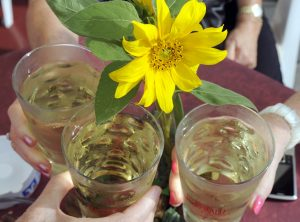 Hände dreier Menschen nehmen sich weinschorle von einem Tisch mit gelber Blume