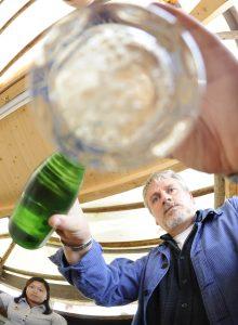 Mann schenkt Wein in ein Glas durch dessen Boden das Bild fotografiert wird