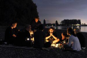 Jugendliche am nächtlichen Lagerfeuer am Rheinufer