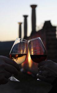 Zwei Hände stoßen mit Weingläsern im Abendlicht an