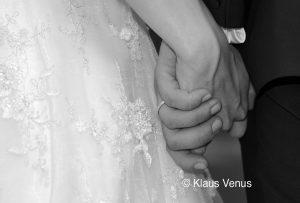 Ineinander verschlungene Hände des frisch vermählten Ehepaars