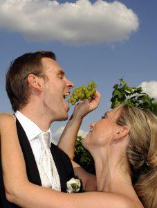Braut füttert Bräutigam mit Trauben