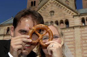 Brautpaar vor Speyerer Dom schaut durch eine Brezel