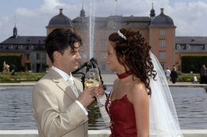 Hochzeitspaar pristet sich vor Springbrunnen und Schwetzinger Schloss mit Wein zu
