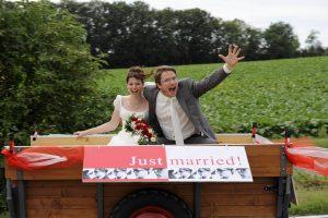 Feierndes Hochzeitspaar auf Anhänger mit Just Married Schild