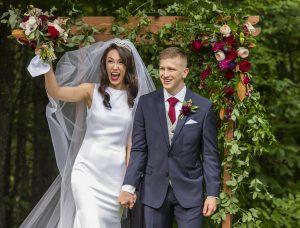 Frisch getrautes Hochzeitspaar kommt durch Blumenbogen