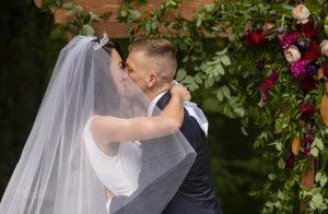 Jochzeitspaar küsst sich unter Blumenbogen