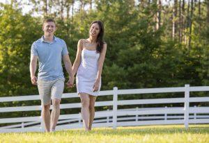 Paar kommt Hand in Hand über Wiese gelaufen, weißer Zaun im Hintergrund