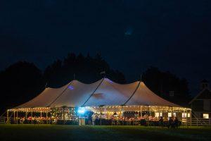 Beleuchtetes Hochzeitszelt bei Nacht auf einer Wiese