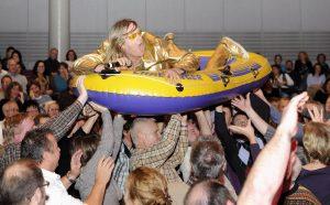 ganz in Gold gekleideter Sänger macht Crowdsurfing in einem Schlauchboot
