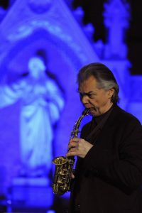 Saxophonspieler vor blau beleuchtetem Innenraum in einer Kirche