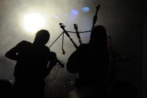 Geieger und Dudelsackspieler im Gegenlicht vom Hintergrund der Bühne gesehen