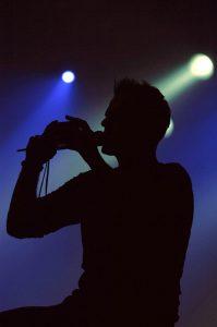 Sänger im Gegenlicht vor blauem Hintergrund