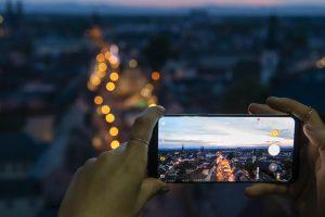 Frauenhände halten Smartphone, das die beleuchtete Maximilianstraße fotografiert, die man im Hintergrund verschwommen in groß sieht