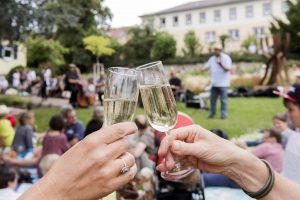 Zwei Hände prosten sich mit Sekt zu, im Hintergrund Sänger und Gäste bei Picknickkonzert