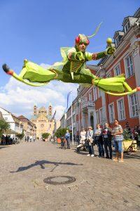 Stelzenläufer im Spagatsprung vor Speyerer Dom und Rathaus