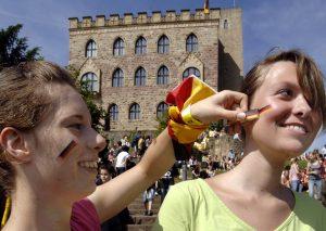 Zwei Mädchen vor dem Hambacher Schloss, die sich die Farben der Deutschlandflagge auf die Wangen malen