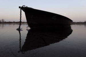 Verankertes Boot im Gegenlicht auf vereistem Wasser