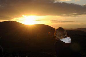 Frau betrachtet Sonnenuntergang im Pfälzer Wald