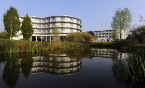 Tagungsgebaeude und Gaestehaus der Deutsche Hochschule fuer Verwaltungswissenschaften, DHV, im Sonnenaufgang in einer Spiegelung in einem Teich