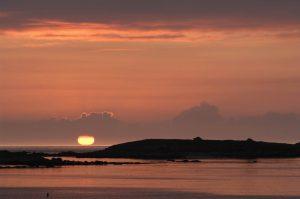 Sonnenuntergang am Strand, glutrot versinkt die Sonne im Meer