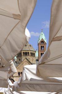 Türme des SPeerer Doms durch beige Sonnenschirme eines Cafés gesehen
