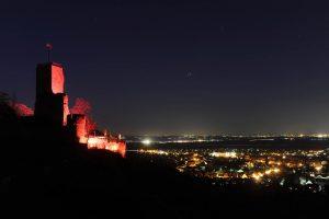Rot beleuchtete Burgruine Wachtenburg bei Nach mit Blick über das erleuchtete Wachenheim