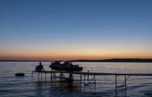 Sonnenuntergang am Lake michigan mit Steg und Boot im Vordergrund