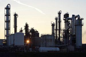 Sonne geht hinter Industrieanlagen auf
