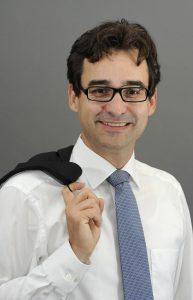 Portrait von Tilo in Hemd und Krawatte mit Sakko über der Schulter