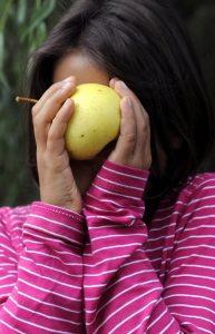 Levke versteckt ihr Gesicht hinter einem Apfel