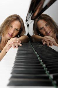 Pianistin Evelyn mit Kopf auf dem Ende der Klaviertasten, spiegelt sich im Korpus des Instruments