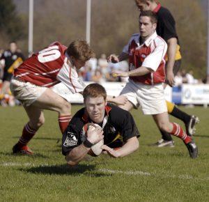Rugby-Spieler fällt mit Ball über die Linie auf die Kamera zu, während hinter ihm mehrere Spieler angerannt kommen