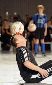 Torwart am Boden versucht Ball wegzuköpfen