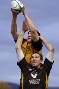 Rugbyspieler springen mit hochgereckten Armen nach oben, om den Ball zu fangen