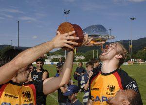 Rugbyspieler trinken nach dem Sieg aus dem Pokal