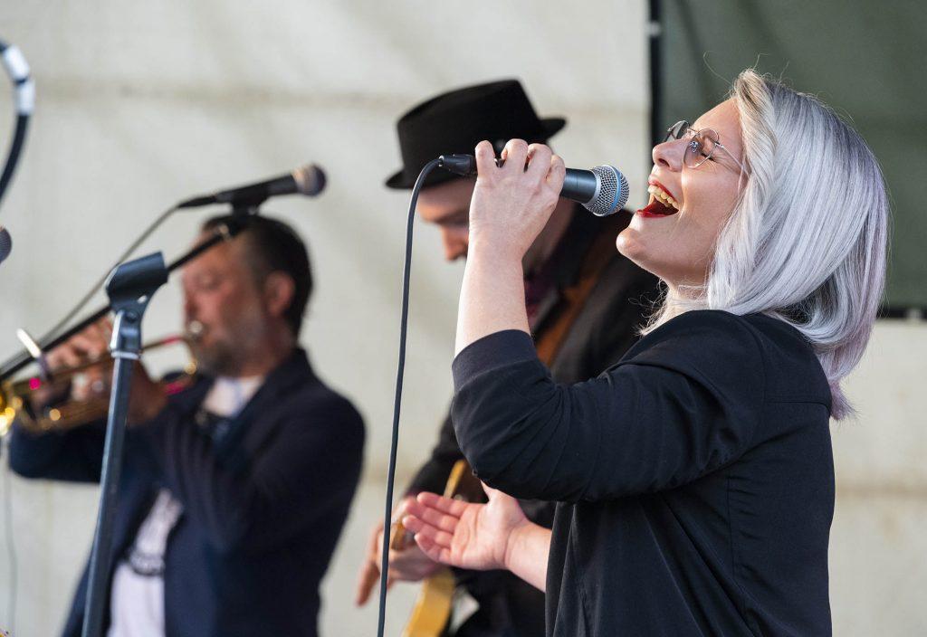 Sarah Lipfert singt im Vordergrund, hinter ihr Bass und Trompete
