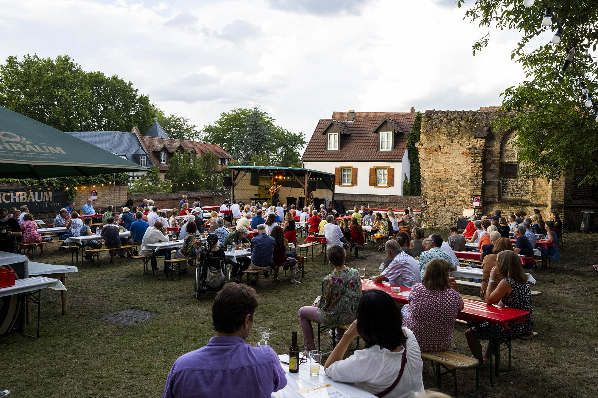 Paradiesgarten der Dreifaltigkeitskirche Speyer mit Bühne und Zuhörern