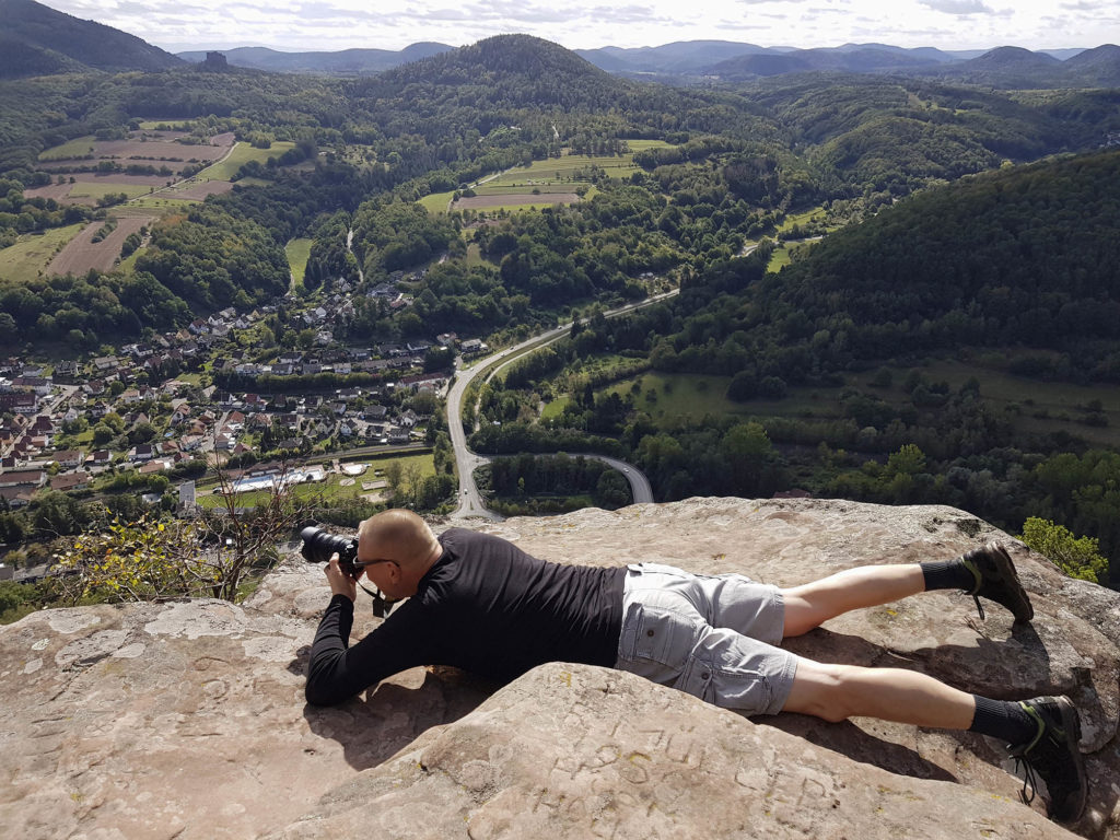 Fotograf Klaus Venus während einer Wanderung auf dem Sommerfels bei Annweiler liegend