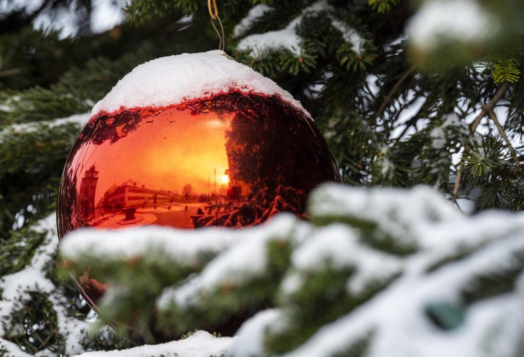 In einer roten Christbaumkugel, die an einem schneebedeckten Baum hängt, spiegelt sich der verschneite Domplatz