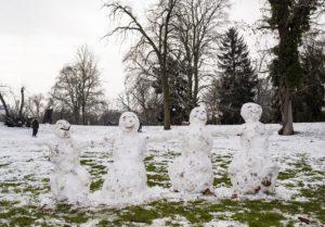 Vier lachende Schneemänner stehen sich an den Händen haltend in einer Reihe auf der verschneiten Domwiese