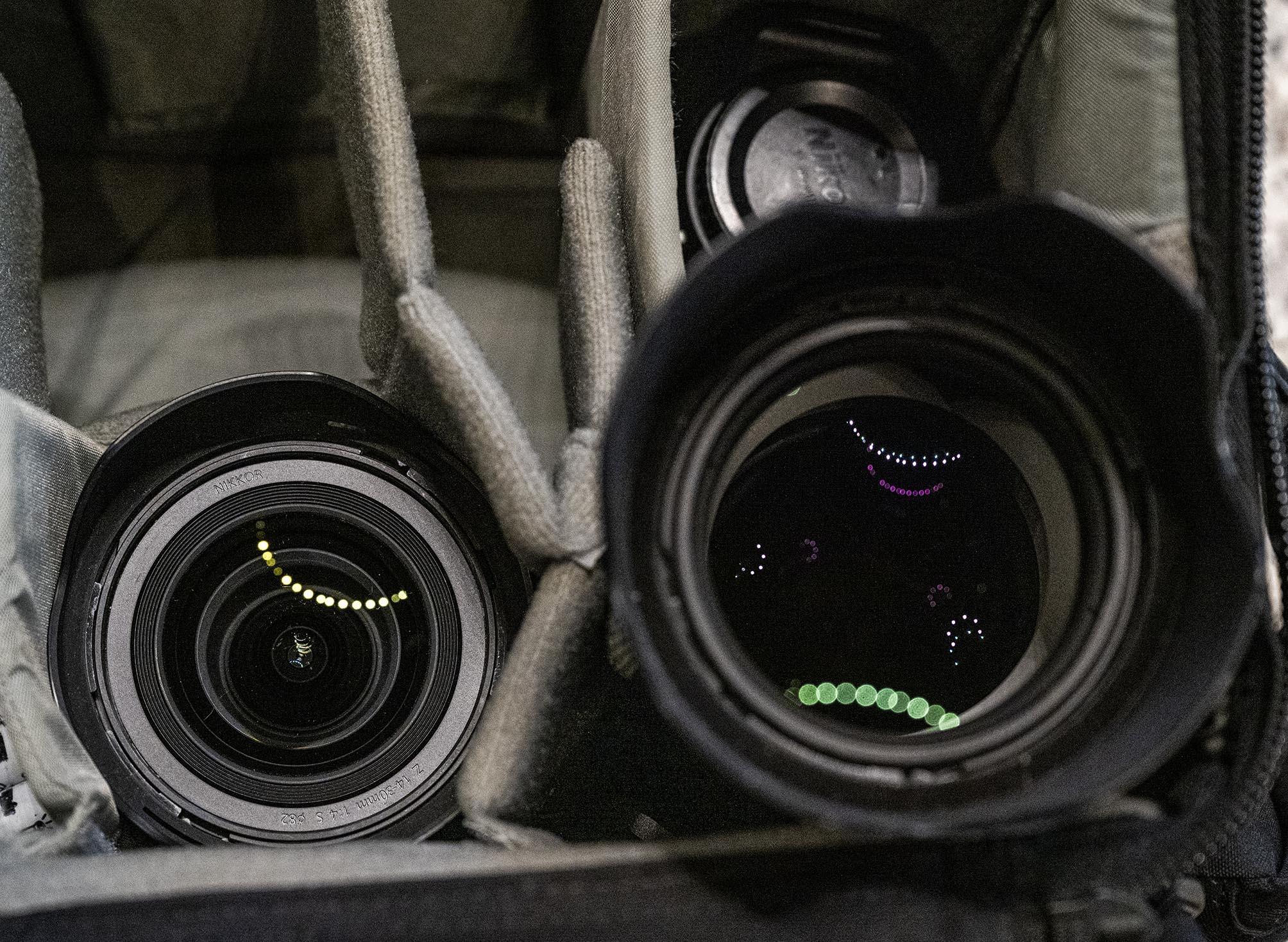 Blick in die fototasche, wo sich in zwei Objektiven Licher spiegeln