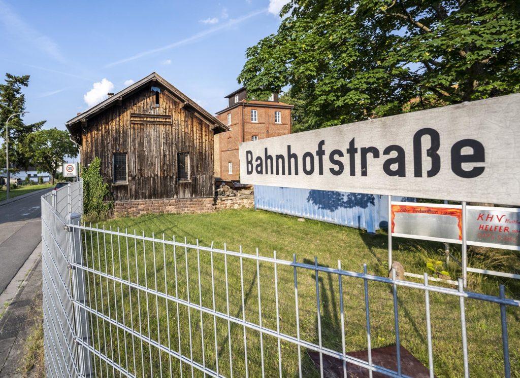 Bahnhofstraße-Schild mit altem Bahnhof Harthausen im Hintergrund
